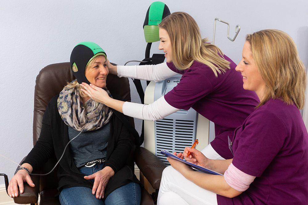 Links im Bild eine Patientin mit DigniCap in einem Behandlungsstuhl. Neben ihr steht die computergesteuerte Kühleinheit, an der eine weitere Kühlkappe hängt. Die Auszubildende Frau Schmidt prüft mit beiden Händen den Sitz der DigniCap. Vorn rechts im Bild sitzt die Medizinischen Fachangestellte Frau Curic mit einem Schreibblock und dokumentiert den Vorgang.