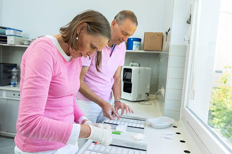 Im praxiseigenen Labor werden Labortests durchgeführt und ausgewertet. Hier sieht man Frau Dr. Hermes und Herr Dr. Simon dabei, wie sie in ihrem Labor gerade Tests auswerten.
