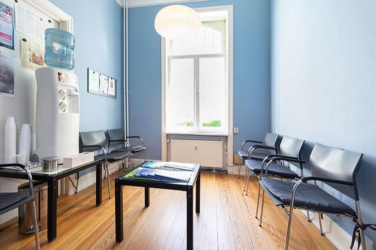 Blick in das Wartezimmer der Onkologischen Praxis von Dr. Simon und Dr. Hermes: im Hintergrund ein Fenster, in der Mitte des Raumes ein Tisch mit Zeitschriften; rechts und links an den Wänden stehen Stühle mit Armlehnen und ergonomisch geformten Rückenlehnen. In der Mitte der linken Stuhlreihe steht ein zweiter Tisch, auf dem sich ein Wasserspender und Plastikbecher befinden.
